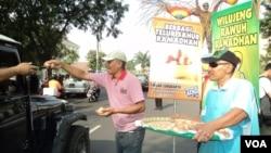 Aksi bagi-bagi telur rebus jelang Ramadan di Solo. (VOA/Yudha Satriawan)