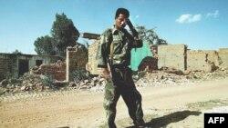 Mwanajeshi wa Eritrea akiwa mbele ya majengo yaliyo haribiwa na mapigano