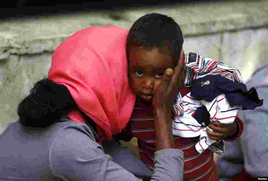 A child is embraced by his mother in front of the migration center next to the Tiburtina station in Rome, Italy. The European Union has tripled funding for rescue missions in the Mediterranean after a shipwreck killed some 800 migrants in April, but it is still trying to find a way to cope with those who arrive, and to relieve the burden on southern countries like Italy and Greece.