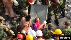 Rescue workers rescue a woman from the rubble of the Rana Plaza building 17 days after the building collapsed in Savar, Bangladesh, May 10, 2013.