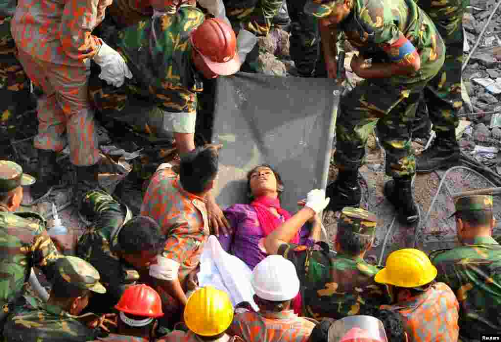 Rescue workers rescue a woman, identified by Bangladeshi media only as Reshma, from the rubble of the Rana Plaza building 17 days after the building collapsed in Savar, Bandladesh. The disaster has killed more than 1,000 people.