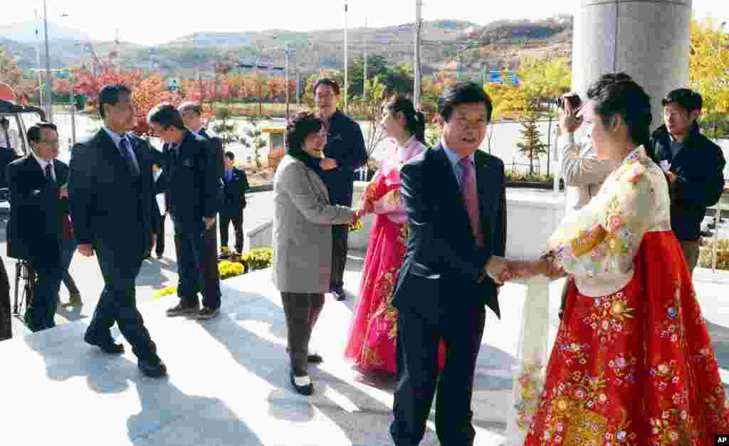 South Korean lawmakers are greeted by North Korean women upon their arrival at the inter-Korean industrial park in Kaesong, North Korea, Oct. 30, 2013.