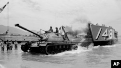 FILE - A U.S. Marine landing craft unloads an M49 on the beach at Da Nang, South Vietnam, April 10, 1965.