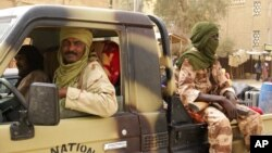 Tuareg fighters from the Movement for the Liberation of Azawad sit in their vehicle, in a market in Timbuktu, Mali, April 14, 2012.