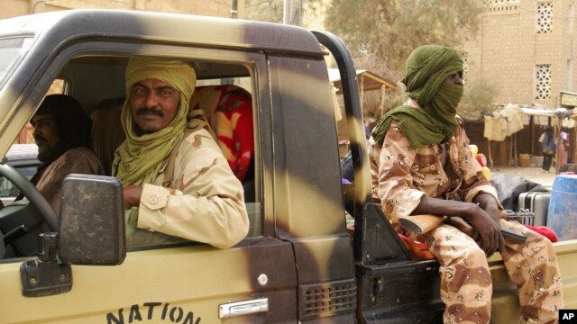 Tuareg fighters from the Movement for the Liberation of Azawad sit in their vehicle in a market in Timbuktu, Mali, April 14, 2012.