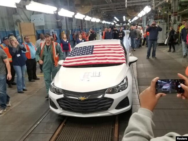 FILE - Employees watch as the last Chevrolet Cruze rolls off the assembly line at the General Motors Co. assembly plant in Lordstown, Ohio, March 6, 2019, in this photo obtained from social media.
