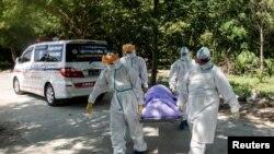 ရန္ကုန္ၿမိဳ႕တြင္ ကိုဗစ္ေၾကာင့္ေသဆံုးသူတစ္ဦးကို သၿဂိဳၤဟ္ဖို႔ သယ္ေဆာင္ေနၾကတဲ့ PPE ဝတ္စံုဝတ္ ပရဟိတလုပ္သားမ်ား။ (ႏိုဝင္ဘာ ၂၅၊ ၂၀၂၀)