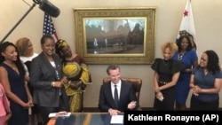 California Gov. Gavin Newsom, middle, signs State Bill, SB-188 Discrimination: hairstyles by Sen. Holly Mitchell of Los Angeles, third from left, that bans discrimination against black people for natural hairstyles.