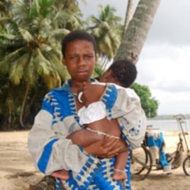 An Ivorian boy holds his baby brother at the Koblakan river crossing in Liberia