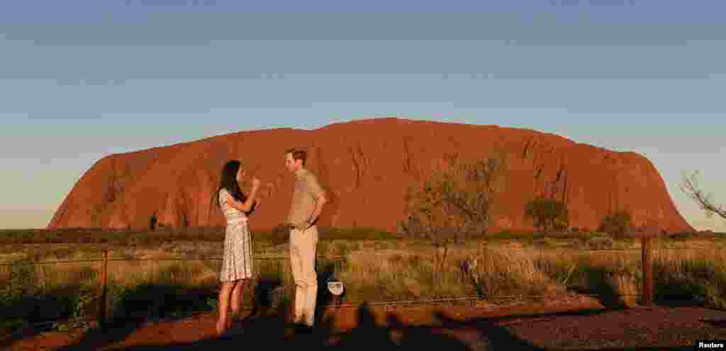 Britain's Prince William and his wife Catherine the Duchess of Cambridge stand in front of Uluru, a UNESCO World Heritage Site, in the Northern Territory of Australia.