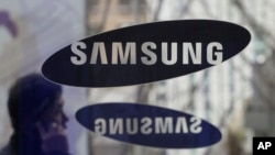 FILE - A man passes by the Samsung Electronics Co. logos at its headquarters in Seoul, South Korea.