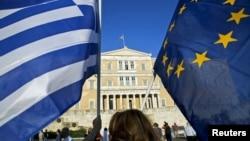 18일 그리스 아테네 의회 건물 앞에서 구제금융 협상 타결을 촉구하는 시위대가 그리스 국기와 유럽연합 깃발을 동시에 흔들고 있다.