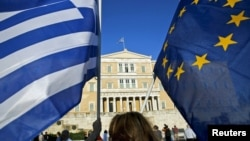 A woman waves a Greek national flag and a European Union flag during a rally outside the Parliament, calling on the government to clinch a deal with its international creditors and secure Greece's future in the Eurozone, in Athens, Greece, June 18, 2015.