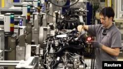 Un employé assemble des moteurs de voiture dans une usine de Stuttgart-Zuffenhausen le 24 janvier 2012.