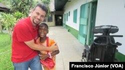 Padre Ricardo Paganini, responsável do Centro Obra Dom Orione, e uma das crianças