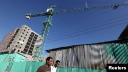 FILE - People walk past office blocks under construction in Ethiopia's capital, Addis Ababa, Jan. 27, 2010.