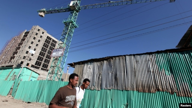People walk past office blocks under construction in Ethiopia's capital Addis Ababa, January 27, 2010.