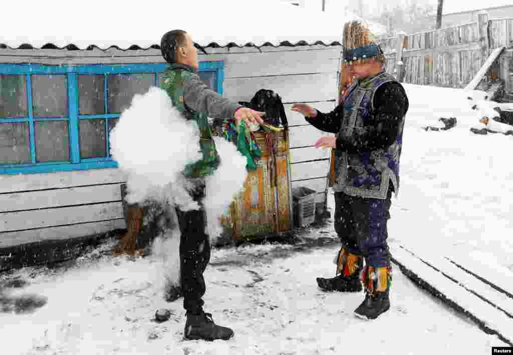 Duger Khomushku (R), a shaman representing the so-called Dungur society, conducts a spiritualistic session with a customer on the exorcism of evil spirits at a court yard of his residence in the town of Kyzyl, the administrative center of the Republic of of Tuva (Tyva region) in Southern Siberia, Russia.