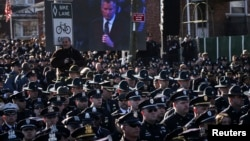 At crowded funeral for slain NYPD Officer Rafael Ramos, many officers turn their backs to shun New York City Mayor Bill de Blasio as he delivers eulogy, Dec. 27, 2014.