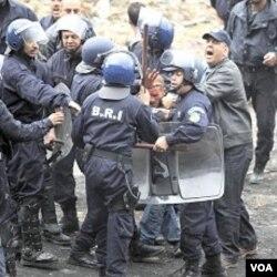 Polisi anti-huru-hara Aljazair menahan seorang demonstran di Oued Koriche, Algiers, Kamis (23/4).