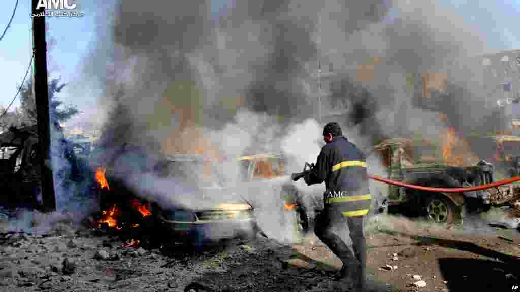 In this citizen journalism image, a firefighter hoses down burning vehicles after a Syrian air strike in Aleppo, Dec. 22, 2013.