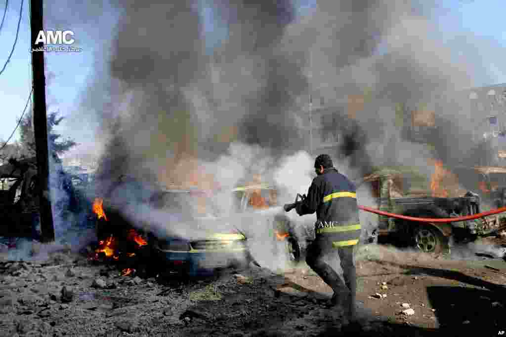 In this citizen journalism image, a firefighter hoses down burning vehicles after a Syrian aircraft pummeled  an opposition neighborhood in Aleppo, Syria, Dec. 22, 2013.