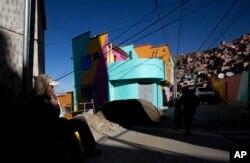En esta fotografía del 31 de mayo de 2019, un trabajador fuma un cigarrillo mientras descansa después de pintar una casa como parte de un proyecto patrocinado por el estado para embellecer el barrio de Chualluma, en La Paz, Bolivia.