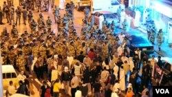 Polisi anti-huru hara menghadap para demonstran di Awwamiya, Arab Saudi pekan lalu.