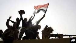 Men stand on top of an armored Egyptian Army vehicle during a protest in Cairo, Jan 29, 2011