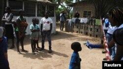 Trabajadores de salud toman la temperatura a un niño que estuvo en contacto con una mujer que murió de ébola, en Monrovia, Liberia, en enero.