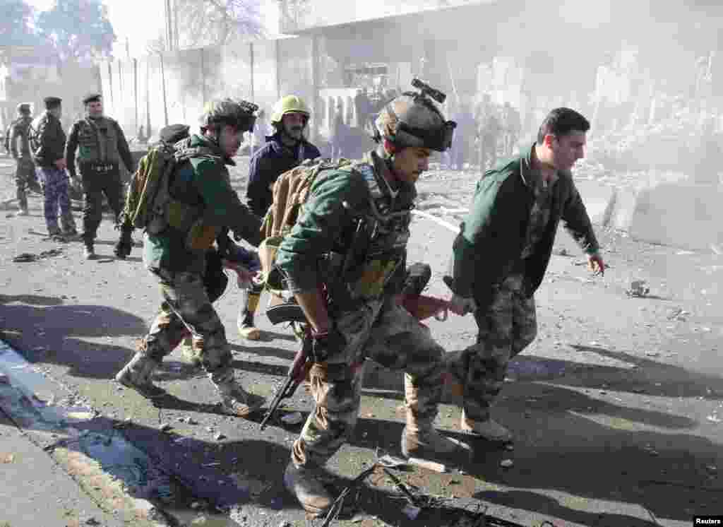 A wounded person is carried by soldiers at the site of a suicide bomb attack in Kirkuk, Iraq, February 3,2013.