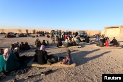 FILE - Displaced families, fleeing violence in Aleppo city and from Islamic State-controlled areas in Raqqa and Deir al-Zor, sit at a school in al-Mabroukeh village in the western countryside of Ras al-Ain, Syria, Dec. 28, 2015.