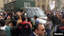Protesters attack a police vehicle driving by an anti-government protest in Cairo, Feb. 22, 2013.