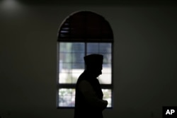 FILE - An imam prays at a mosque in Chino, California, Nov. 18, 2016. Targeting clerics opposed to the Islamic State in a new propaganda campaign, the jihadist group is thought to have launched an effort aimed at deligitimizing them, especially in the eyes of young Muslims.