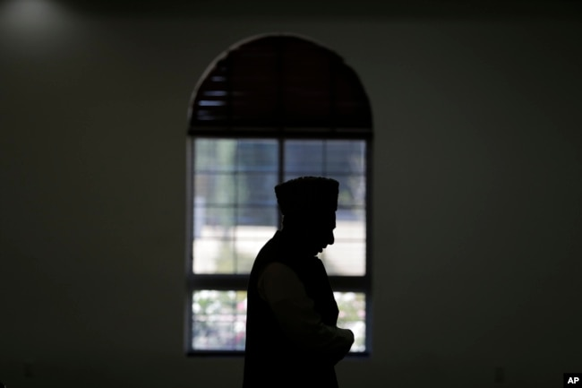FILE - An imam prays at a mosque in Chino, California, Nov. 18, 2016. Targeting clerics opposed to the Islamic State in a new propaganda campaign, the jihadist group is thought to have launched an effort aimed at deligitimizing them, especially in the eye