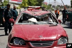 An Afghan man drives his damaged car after a suicide attack in Kabul, Afghanistan.
