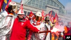 Francuski članovi sindikata pale baklju tokom demonstracija ispred zgrade u kojoj je počeo samit EU u Briselu, 14. mart 2013.
