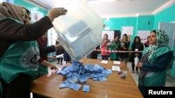 سن 2014 کے عام انتخابات کے موقع پر کابل کے ایک پولنگ اسٹیشن میں ووٹوں کی گنتی کی تیاری کی جا رہی ہے۔