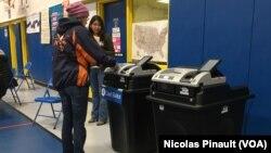 Une femme vote sur un ordinateur au bureau de vote de Barcroft, à Arlington, Virginie, le 8 novembre 2016 (VOA/Nicolas Pinault)