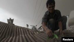 Penduduk desa membersihkan atap rumahnya dari debu semburan Gunung Sinabung seperti terlihat di Desa Sibintun, Kabupaten Karo, Sumut, 14/1/2014.