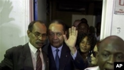 "Haiti's former dictator Jean-Claude ""Baby-Doc"" Duvalier, center, waves to the media upon his arrival at the Toussaint Louverture international airport in Port-au-Prince, Haiti, 16 Jan. 2011."
