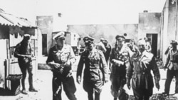 Field Marshal Erwin Rommel, center, walking through a desert village in Egypt