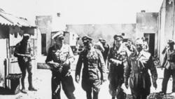 Field Marshal Erwin Rommel, center, walking through a desert village in Egypt