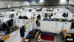 A gym is separated into cubicles where refugees sleep on cots, in a camp near Holzdorf, Germany, Nov. 29, 2015. Residents say the lack of outside interaction makes them feel isolated, and more like prisoners than asylum-seekers. (VOA News)