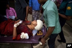 FILE - Rafida Ahmed, wife of Avijit Roy, is being rushed to hospital on a stretcher after she was seriously injured by unidentified attackers, in Dhaka, Feb. 25, 2015.
