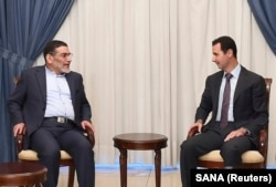 FILE - Syria's President Bashar al-Assad, right, meets Admiral Ali Shamkhani, Iran's Supreme National Security Council Director, in Damascus, Sept. 30, 2014.