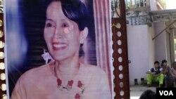 Seorang pendukung Aung San Suu Kyi memasang posternya di depan markas partai di Rangoon, Birma.