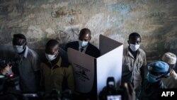 Le président de la République centrafricaine Faustin Archange Touadera dans un isoloir entouré par la garde présidentielle au bureau de vote du lycée Barthélemy Boganda dans le 1er district de Bangui, en RCA, le 27 décembre 2020