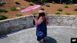 Karla Hailer, a fifth-grade teacher from Situate, Massachusetts, makes a video of the Proctor's Ledge Memorial before the noon dedication of the site July 19, 2017, at the site where five women were hanged as witches 325 years ago.