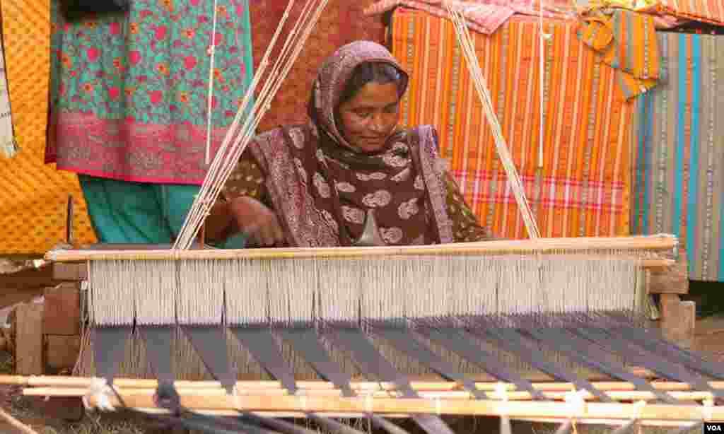 کھڈی پر کپڑے بنتی ایک خاتون